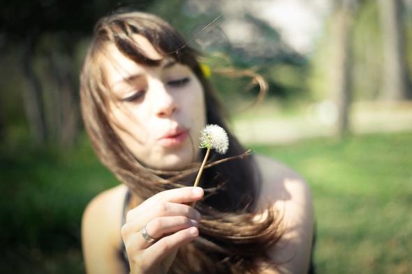 綿毛を飛ばす女性